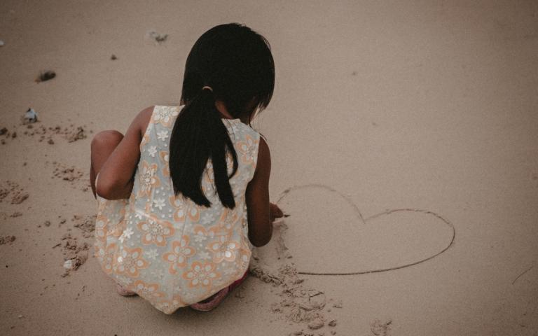 Jugando con arena.Una niña con un vestido de flores, se encuentra agachada en la arena de una playa realizando una silueta de un corazón, con un objeto que se encontro en la playa. foto por Jakob Owens, stocksnap.io