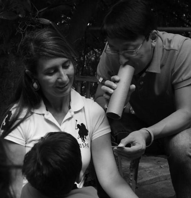 Familia fortaleciendo el vínculo afectivos, un papá en una actividad de lluvia de luna utilizando un tubo de reciclaje para contarle un verso a su pequeño.