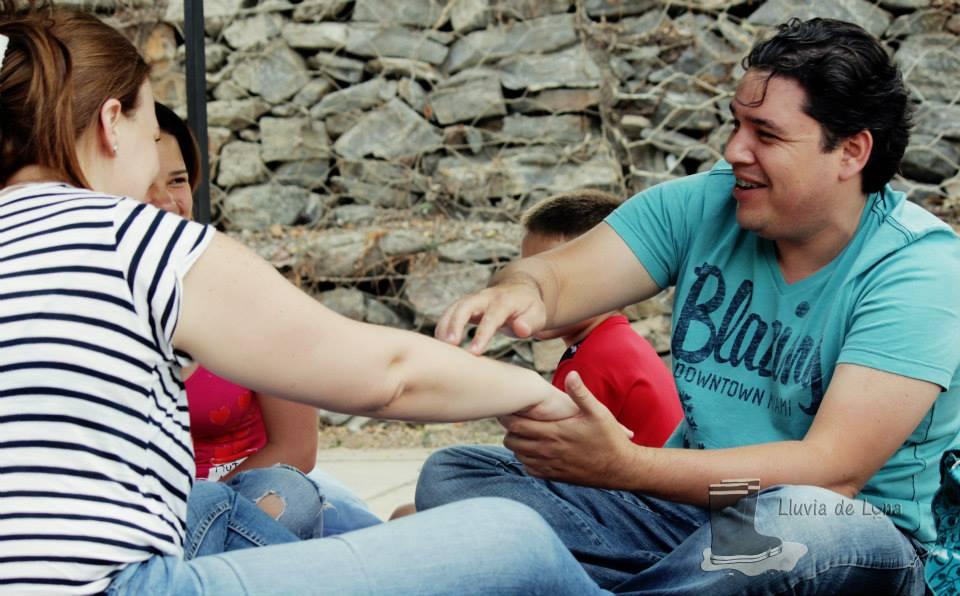 Padres fortaleciendo los vínculos afectivos, un padre jugando en el brazo de su esposa, contándole un cuento con el cuerpo. Felices por que están fortaleciendo vínculos entre ellos.